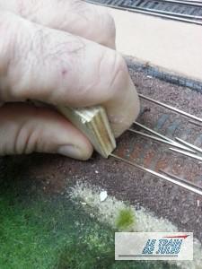 Nettoyer les rails avec la tranche d'un morceau de contreplaqué