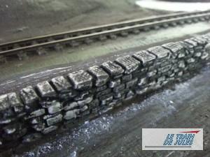 Un mur de pierre HO teinté en noir.
