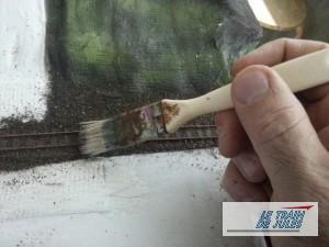 Egalisation du ballast au pinceau.