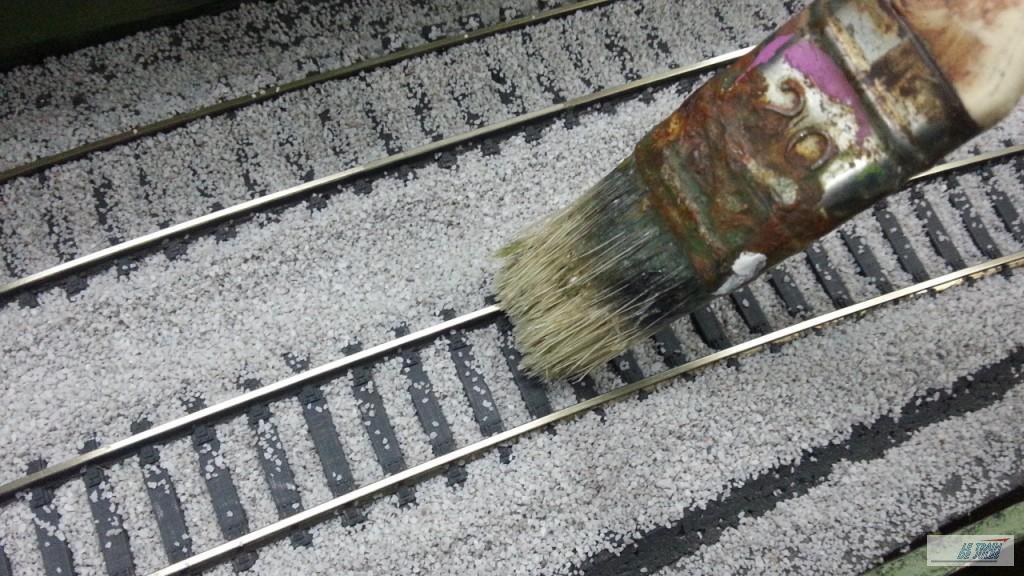 Coup de pinceau pour égaliser le ballast sur les traverses